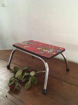 Petit banc repose piedsen formica rouge fleuri.