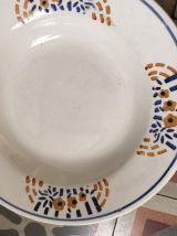 Huit assiettes creuses dépareillées en brun et bleu.