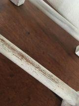 Banc en bois repose-pieds patiné blanc.