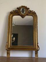 Miroir doré fin 19ème avec fronton décoré. 100x60.