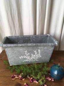 Jardinière en zinc avec décoration florale.