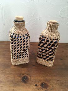 Lot de deux bouteilles bleues gainées de rotin tressé.