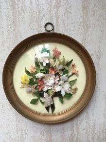 Cadre rond de fleurs artificielles au verre bombé.