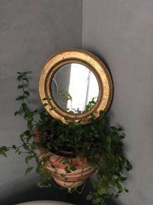 Miroir rond au cadre doré.