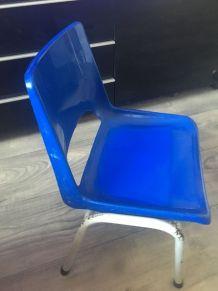 Chaise coque en plastique et pieds métal. Elle porte l'estam