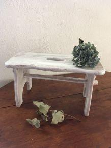 Petit banc en bois dans sa patine blanche.