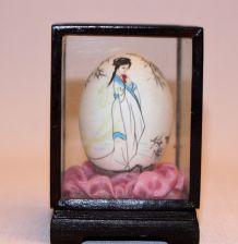 Oeuf peint décor chinois dans une vitrine.  Motif femme.