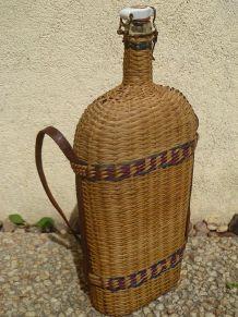 bouteille ancienne en verre recouverte d'osier ,vintage 1960