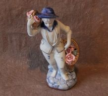 Figurine en porcelaine jeune homme aux paniers de roses