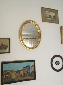 Miroir ovale au cadre en bois doré.