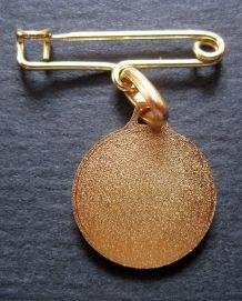Médaille + épingle en métal doré avec pour tour diamanté .