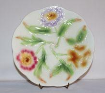 Assiette en faïence barbotine à motifs de fleurs.