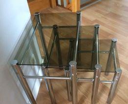Tables gigognes en verre fumé et armature chromée .