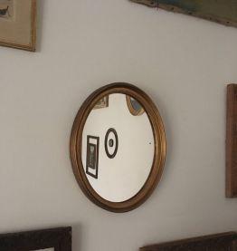 Miroir ovale en bois doré.