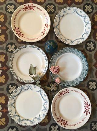 Six assiettes plates dépareillées en vert bleuté et rouge.