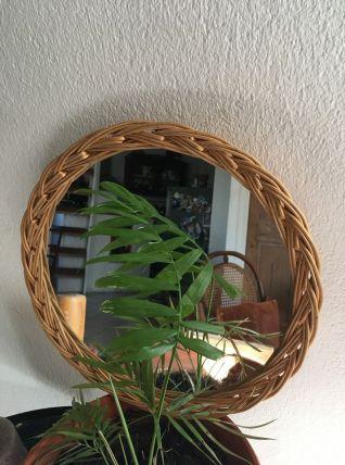 Miroir rond à la bordure en osier tressé.