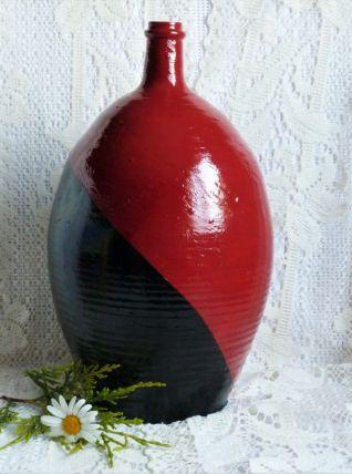 En rouge et noir : ancienne cruche de ferme peinte.