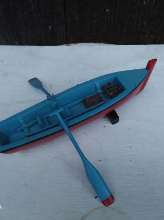 barque bleue avec rames, filet et bouée
